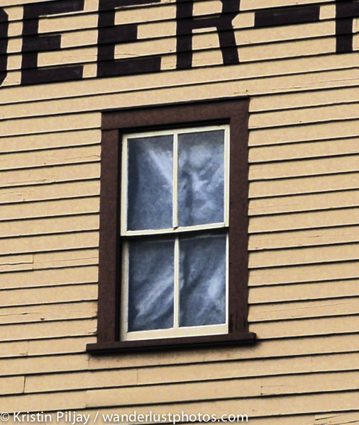 "crop of photo of hotel of ""face"" seen in the third floor widow that has been closed off for 60 years"
